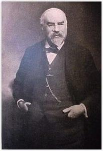 Walter Brind Waldron, standing, hands in waiscoat pocket